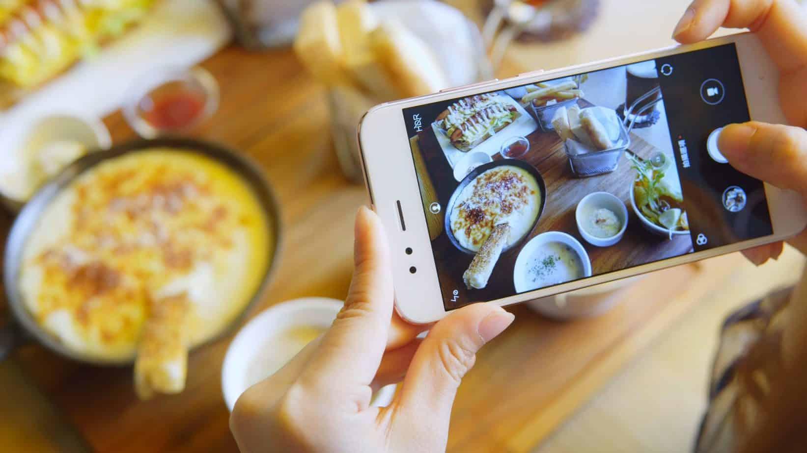 closeup hand holding phone shooting food photograph