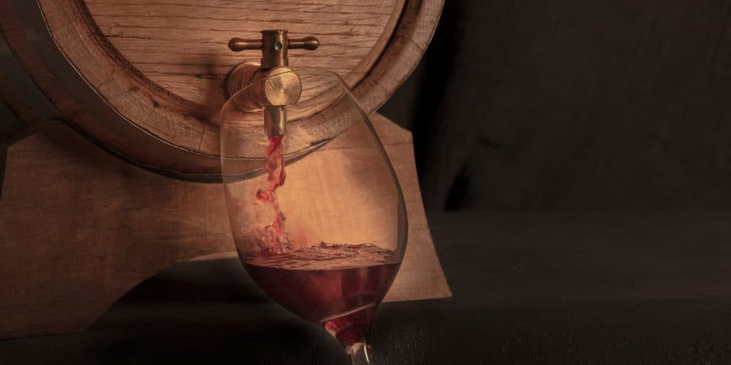 Pouring wine into a glass from an oak barrel, a toned panorama on a dark background with copy space